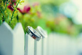 Wedding rings on wooden fence close up — Stock Photo