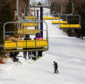 Skier & Snowboarders going up a mountain in yellow chairlift — Stock Photo