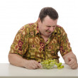 Fat man grimaced sour grapes — Stock Photo