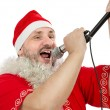 Happy guy in Santa Suit singing in microphone — Stock Photo