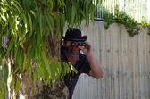 Cowboy in bandana looking through binoculars — Stock Photo