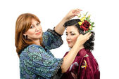 Fox-coloured hairstylist putting roses and butterfly in her hair — Stock Photo