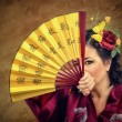 Woman with flowers hair looking at you through the Asian fan — Stock Photo #48152243
