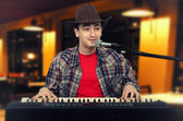 Photo of young cowboy playing the digital piano at pub — Stock Photo