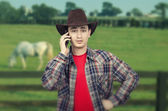 Portrait of lively young cowboy calling on phone — Stock Photo
