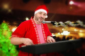 Portrait of Santa Claus playing electric piano — Stock Photo