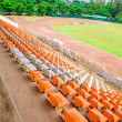 Stadium seats in arena with green field — Stock Photo