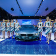 Stock Photo: Unidentified many modelling posted with BMW 420d Coupe Sport