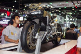 Unidentified people look at Ducati 1199 motorcycle display on stage — Stock Photo