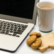 White work desk with a laptop computer, bread cookie and cup of — Stock Photo #43042545