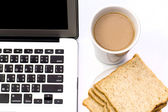 White desk with laptop computer and cup of coffee with bread — Stok fotoğraf