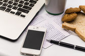 Laptop with cellphone , book bank, cookie, bread and cup of coff — Stockfoto