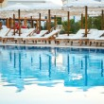 Lounge chairs near the pool at sundown time horizontal — Stock Photo