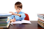 Boy writes and takes a book at the same time — Stock Photo