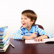 Laughing boy sitting at the desk with many books — Stock Photo