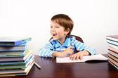 多くの書籍と、机に座っている少年を笑ってください。 — ストック写真