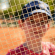 Smiling teenage girl looking through the net of a tennis racket — Stock Photo #45836755