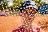 Smiling teenage girl looking through the net of a tennis racket — Stock Photo