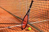 Tennis ball and racket are near the net horizontal side view — Stock Photo