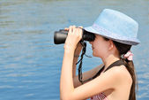 Teen girl looking through binoculars side view — Stok fotoğraf