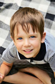 Cheerful boy sitting on carpet and looking from the bottom up — Stock Photo
