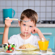 Sad little boy sits at the dining table and looking spaghetti — Stock Photo #51465297