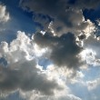 The sun's rays coming out from behind the clouds on a blue sky — Stock Photo