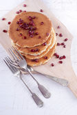 Pancake with pomegranate seed on wooden board — Stock Photo