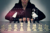 Playing Chess Against a Business Woman with Floating Financial Graphics — Stock Photo