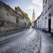 An empty street leading to a church tower — Stock Photo