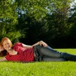 Beautiful woman laying in a park — Foto Stock