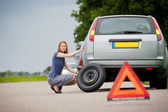Driver fixing flat tire — Stock Photo