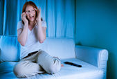 Woman on the phone while watching TV — Stock Photo