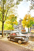A retro car parked near a water canal — Foto Stock