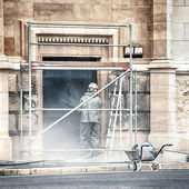 Worker cleaning the facade of a building — Stock Photo