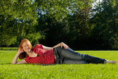 Beautiful woman laying in a park — Stock Photo