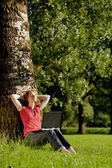 Woman with a notebook in a park — Stock Photo