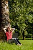 Vrouw met een laptop in een park — Stockfoto