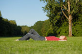 A beautiful woman laying in the park — Stock Photo