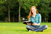 Young Believer with a Bible in a Park — Stock Photo