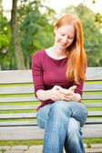 Woman Using Cell Phone in a Park — Stock Photo