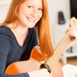 Happy Woman with a Guitar at Home — Stock Photo #32767741