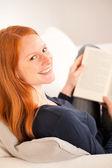 Femme heureuse avec un livre à la maison — Photo