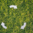 Recycling Arrows on Green Grass — Stock Photo #50410573