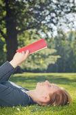 Mujer leyendo un libro al aire libre — Foto de Stock