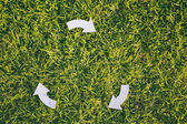 Recycling Arrows on Green Grass — Stock Photo