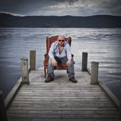 Homme en fauteuil sur une jetée — Photo