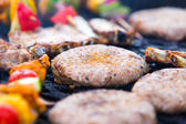Barbecue with hamburgers and skewers — Stock Photo