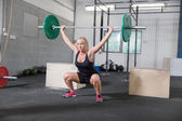 Woman trains squats at crossfit center — Stock Photo