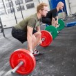 Постер, плакат: Two men train deadlift at fitness gym center